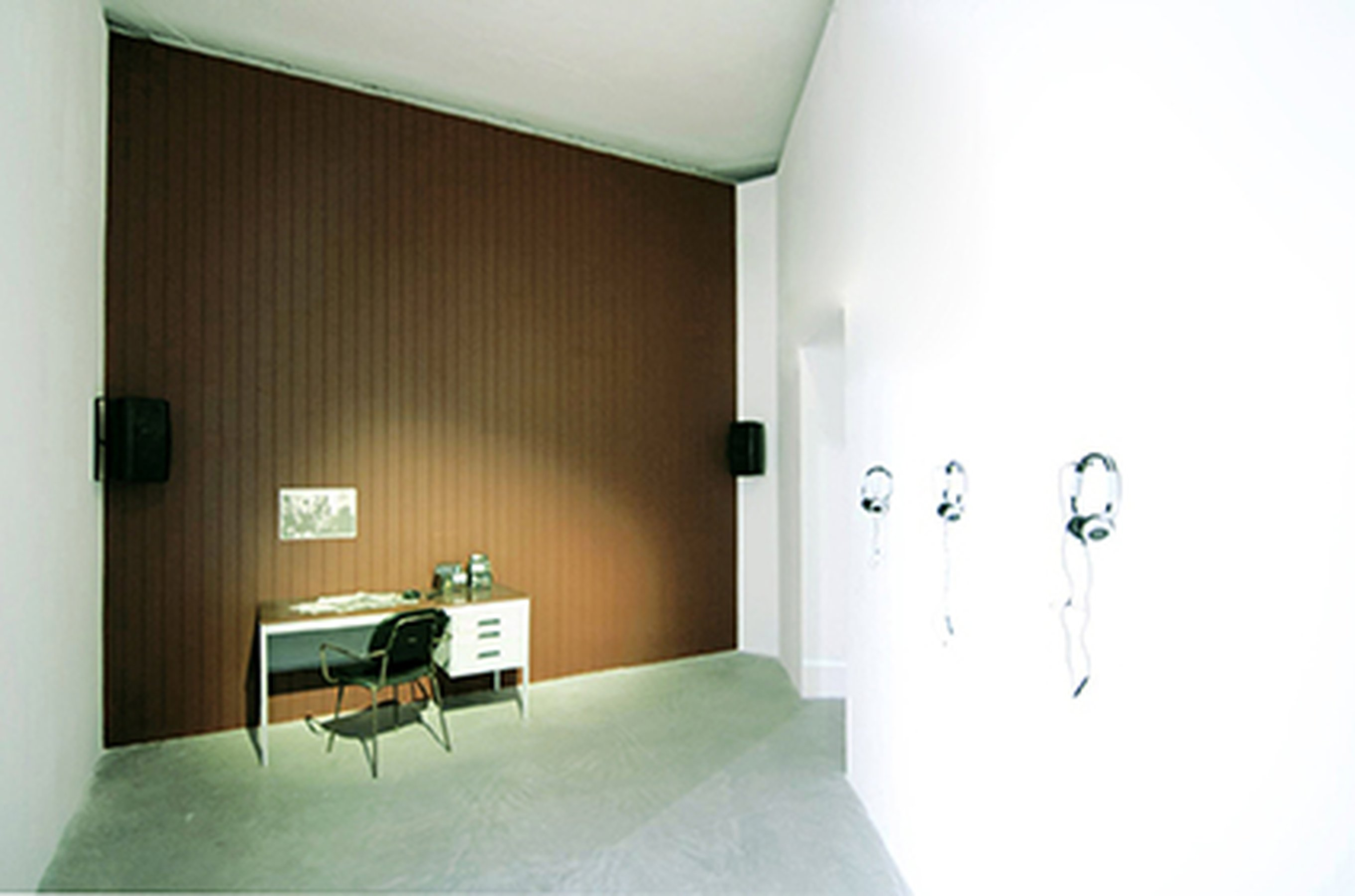Estman Radio Drama, 2011 Installation: painted wood wall, desk, chair, radio, 4 CD players, 4 headphones Dimensions determinated by the space Installation view at 54th Biennial of Venice, ILLUMINATIONS, Venice (IT)